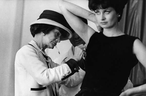 July or August 1961, Paris, France --- Fashion designer Coco Chanel adjusts the armhole of a model's dress with an assistant. --- Image by © Douglas Kirkland/CORBIS